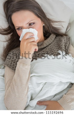 Sick woman holding tissue to nose on the couch - stock photo