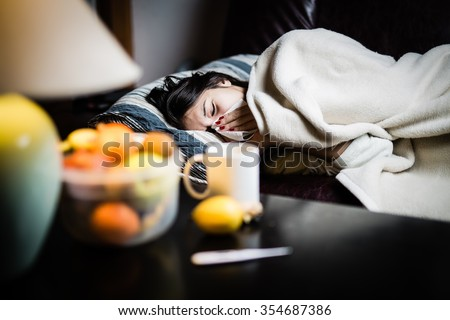 Sick woman in bed,calling in sick,day off from work.Thermometer to check temperature for fever.Vitamins and hot tea in front.Flu.Woman Caught Cold.Virus.Sick woman laying in bed under wool blanket  - stock photo