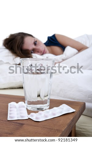 Sick woman in bed, looking at a glass of water, and two blister strips with pills - stock photo