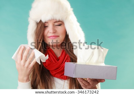 Sick woman in fur hat sneezing in tissue. Ill girl caught winter cold flu in studio on green. - stock photo