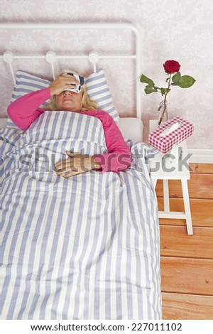 Sick woman in pink pajama with migraine, tissues and a rose lying in bed with washcloth - stock photo
