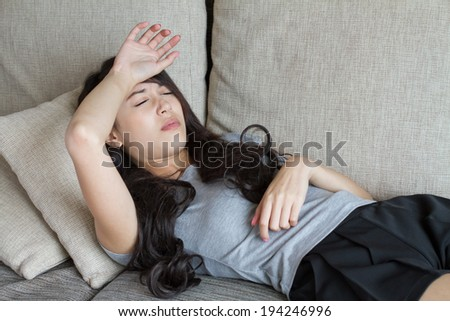 sick woman, resting and lying down in home, indoor scene - stock photo