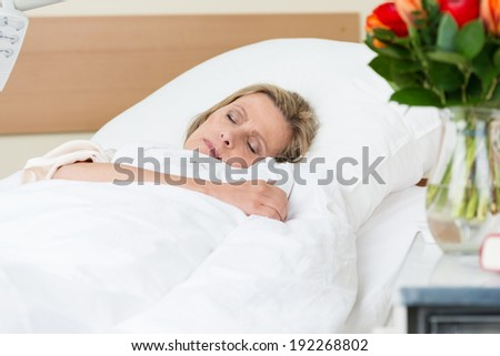 Sick woman resting peacefully in hospital lying asleep in a bed on a ward as she recuperates from an injury or illness - stock photo