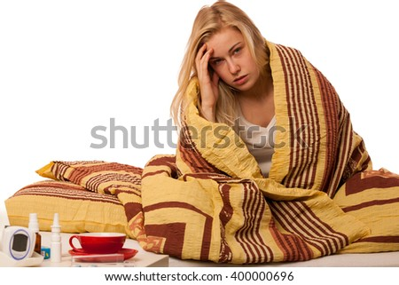 Sick woman sitting on bad wrapped in a blanket feeling ill, has flu, fever and headache. - stock photo