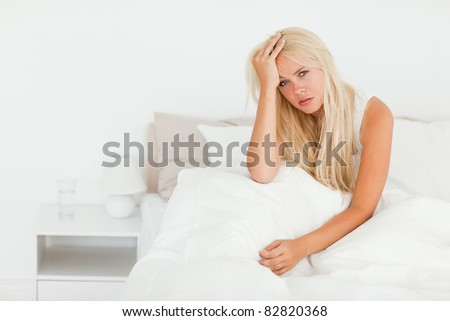 Sick woman sitting on her bed while waking up - stock photo