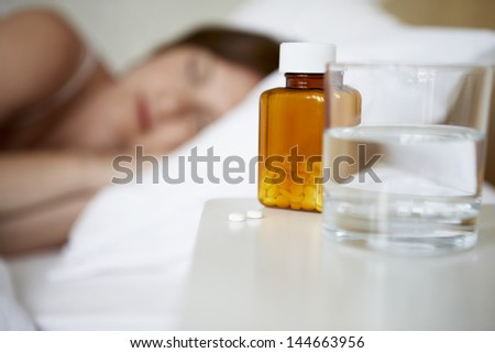 Sick woman sleeping in bed with focus on pill bottle and water glass in foreground - stock photo