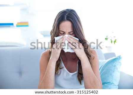 Sick woman sneezing on sofa at home - stock photo