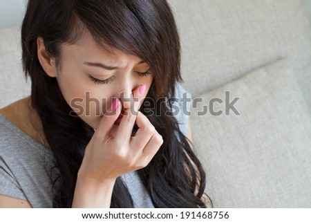 sick woman suffers from flu, cold, running nose, asian caucasian indoor scene - stock photo