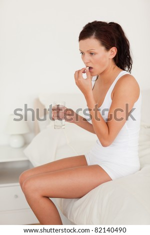 Sick woman taking medicine in her bedroom