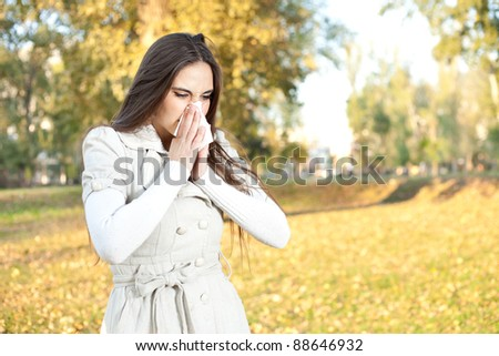 Sick woman with a cold blowing into tissue, outdoor - stock photo