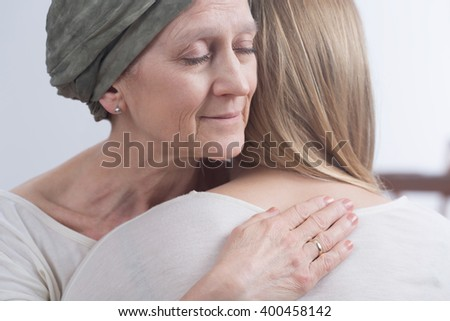 Sick woman with cancer hugging her young daughter - stock photo