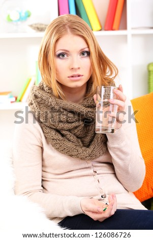 Sick woman with cold sitting on sofa