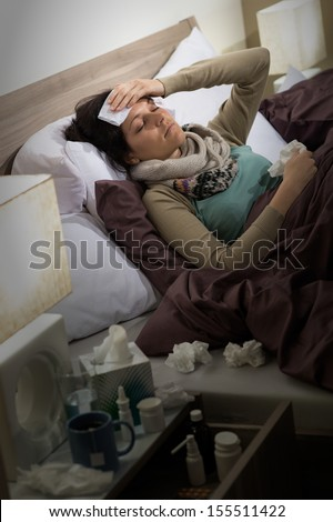 Sick woman with flu lying in bed suffering from headache - stock photo