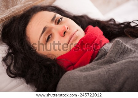 Sick woman with virus. Closeup image of depressed young woman with red nose lying in bed with thick scarf on her neck and looking upset - stock photo