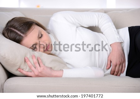 Sick woman. Young woman lying in bed while medicines laying on the foreground - stock photo