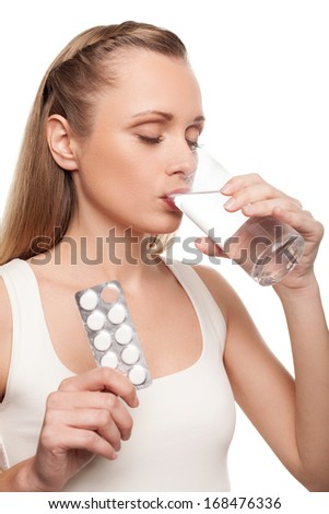 Sick woman. Young woman taking pills and keeping eyes closed while standing isolated on white - stock photo
