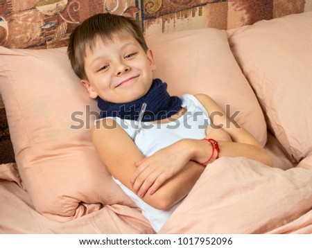 Sick young boy measures the temperature in the bed