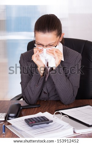 Sick young businesswoman blowing her nose in office - stock photo