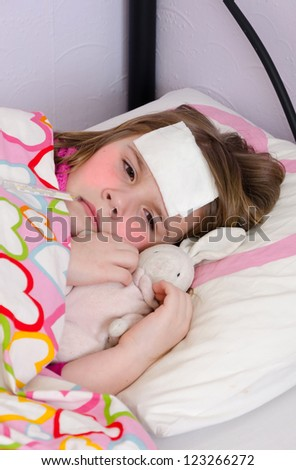 Sick young girl in bed - stock photo