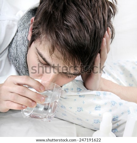 Sick Young Man drinks the Water on the Bed closeup - stock photo