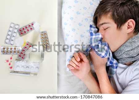 Sick Young Man sleeping on the Bed near the table with a pills - stock photo