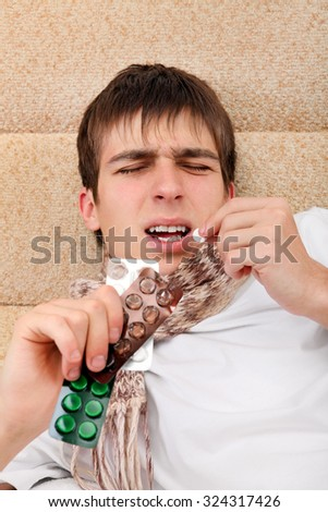 Sick Young Man take a Pill on the Bed at the Home - stock photo