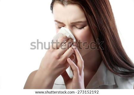 sick young woman blowing her nose isolated on white background - stock photo