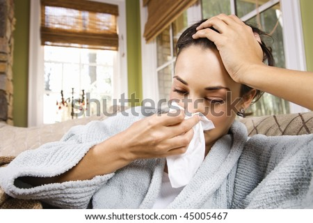 Sick young woman blows her nose into a tissue. Horizontal shot. - stock photo