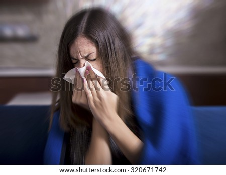 Sick young woman is coughing and blowing - stock photo