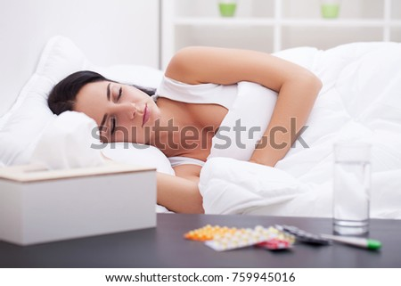 Sick young woman is coughing on the bed