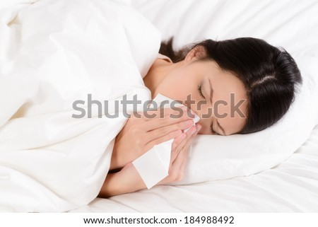 Sick young woman lying in her clean white bed blowing her nose on a tissue conceptual of healthcare and seasonal flu and chills, rhinitis or an allergic reaction in hay fever - stock photo