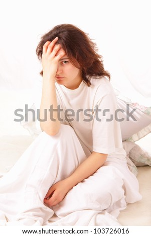 sick young woman sitting in bed - stock photo