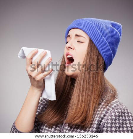 Sick young woman with a flu, sneezing closeup  over grey - stock photo