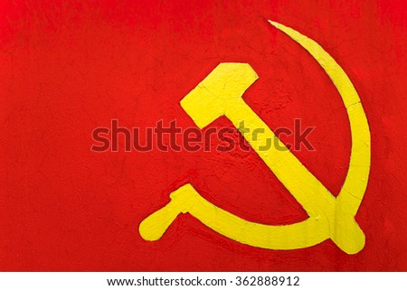 sickle and hammer on a red wall - stock photo