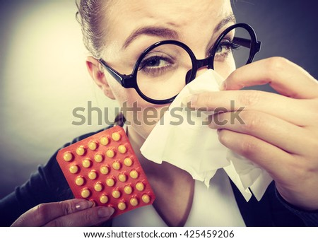 Sickness and diseases at work. Young unhealthy businesswoman with tissue having flu grippe. Secretary accountant with illness and pills spreads disease.