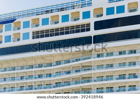 Side angle view on large cruise liner ship.  Cropped side angle view on large multilevel blue and white cruise liner ship with railings and terraces under blue sky