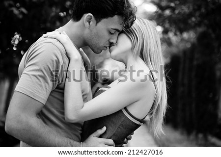Side black and white portrait of a passionate romantic young couple kissing and embracing while in a park on holiday. Young people romantic lifestyle and love, outdoors. - stock photo