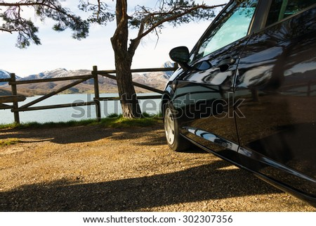 Side black car, parked in a rest area or lookout road, in the shade of a tree and a fence of wooden posts. Against a backdrop of mountains and lake or swamp  - stock photo