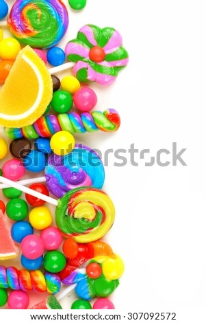 Side border of an assortment of colorful candies against a white background - stock photo