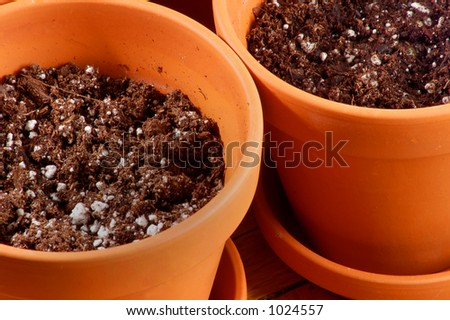 Side by Side Clay Flower Pots Filled with Soil - stock photo
