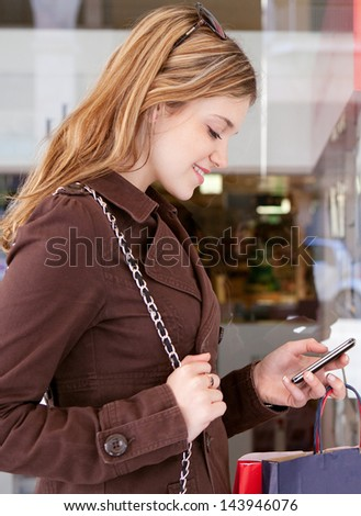 Side close up portrait of a young teenager tourist visiting the city and carrying paper shopping bags while leaning on a fashion store window, using her smartphone device and smiling. - stock photo