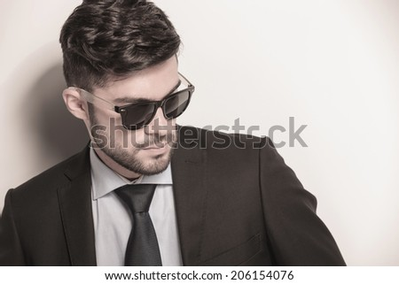 side closeup picture of a sexy young business man wearing sunglasses and looking away - stock photo