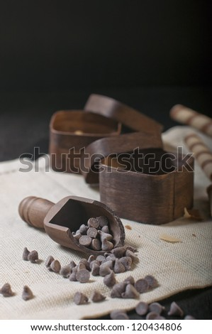 Side closeup view of wooden scoop with chocolate drops and two boxes on beige napkin and dark background. - stock photo