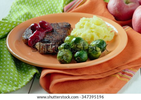 Side dish of Brussels sprouts and mashed potatoes with a chop.