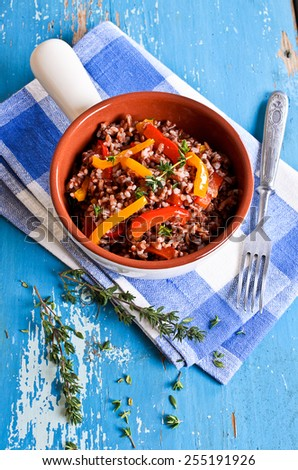 Side dish of red rice with paprika and thyme - stock photo
