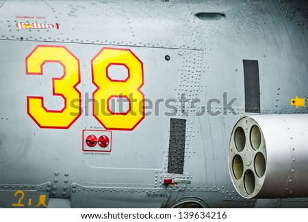 Side of helicopter with red and yellow drawn number 38 and text with russian letters on it. Close-up of military air transport with missile. Army chopper with rockets. Air forces of Russia. - stock photo