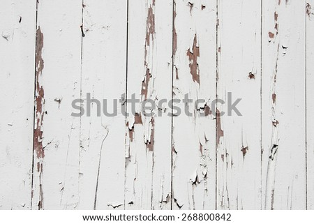 Side of old barn with peeling white paint.