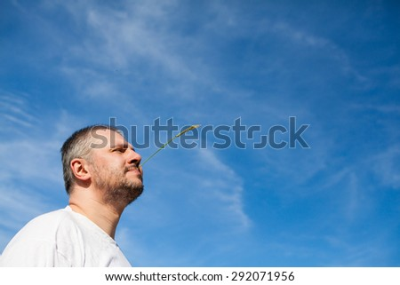 Side portrait low angle view of a man with beard chewing stem and standing and looking ahead against a blue sky with white clouds - stock photo