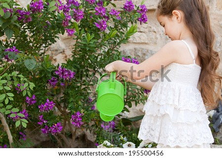 Side portrait of a beautiful young child girl holding a watering can and watering the plants in her holiday home garden, focused outdoors. Kid helping with home duties while on vacation, lifestyle. - stock photo