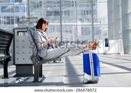 Side portrait of a business woman sitting with bag and mobile phone at airport - stock photo